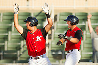 Rangel Ravelo #24 and Joe De Pinto #2 celebrate after De Pinto scored the winning run in the bottom of the 9th inning against the Hickory Crawdads at CMC-Northeast Stadium on April 8, 2012 in Kannapolis, North Carolina.  The Intimidators defeated the Crawdads 12-11.  (Brian Westerholt/Four Seam Images)