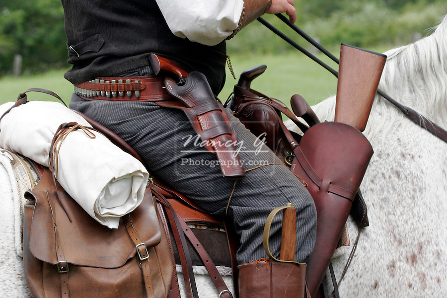 A cowboy on horseback riding in a 1800s western reenactment