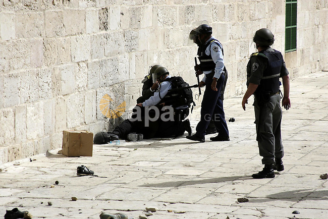 An Israeli soldiers stand around an injured soldier during clashes with Palestinian stones-throwers on the compound known to Muslims as al-Haram al-Sharif and to Jews as the Temple Mount in Jerusalem's Old City March 5, 2010. Israeli police and Palestinians clashed near Jerusalem's flashpoint al-Aqsa mosque on Friday and about 30 people were injured, Israeli police and Palestinian medical workers said . Photo by Mohamar Awad