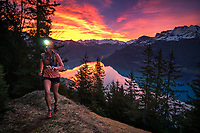 A trail runner using a headlamp at sunrise above the Brienzersee , with a dramatic sky above. Interlaken, Switzerland