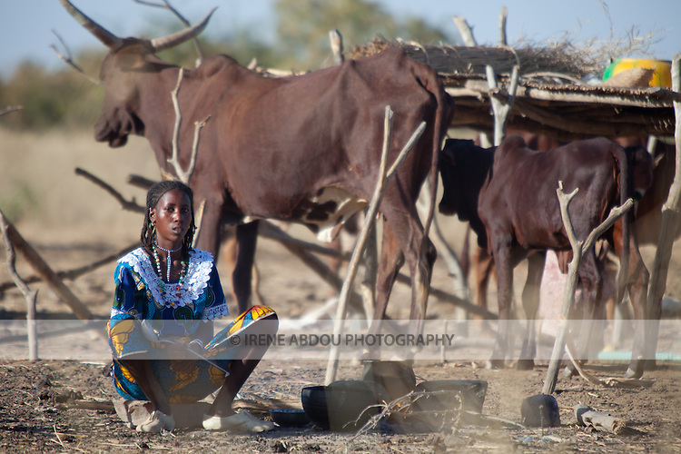 In the seasonal village of Bantagiri in northern Burkina Faso, a Fulani woman cooks breakfast outdoors on the fire.  The Fulani are traditionally nomadic pastoralists, crisscrossing the Sahel season after season in search of fresh water and green pastures for their cattle and other livestock.