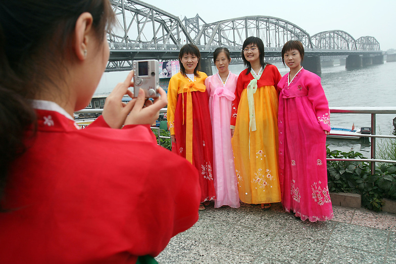 Chinese women dress up in traditional Korean dress and take phots of themselves on the Sino-Korean border from the town of Dandong July 9, 2006. After Pyongyang defied world opinion and test-fired seven missiles last week, Japan formally introduced a U.N. resolution, co-sponsored by the United States, Britain and France, to impose sanctions against its missile program.. DPRK, north korea, china, dandong, border, liaoning, democratic, people's, rebiblic, of, korea, nuclear, test, rice, japan, arms, race, weapons, stalinist, communist, kin jong il