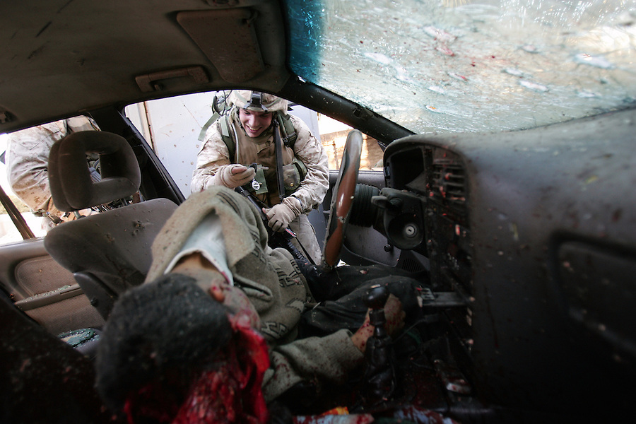 After a long day that began with an insurgent ambush and continued through hours of hit-and-run fighting, a Marine with Golf Co., 2/5 inspects a car driven by man shot to death as he sped through deserted streets towards the MarinesÕ parked vehicles in Ramadi on Jan. 20, 2005. Marines said the man failed to respond to warning shots or flares. A search of the car turned up a ringing cell phone but no weapons or explosives. This happens all to often in Iraq when drivers fail to stop and U.S. forces donÕt hesitate to shoot Ð barely avoidable deaths from which no one benefits.