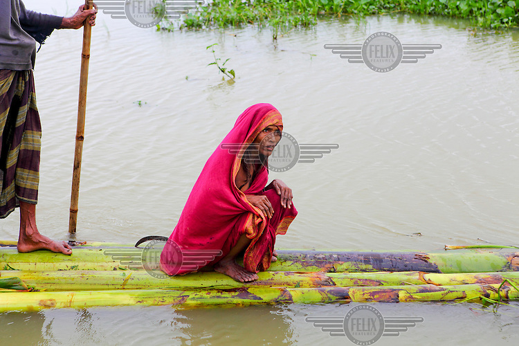 Momtaj Begum (35) is crossing water by help of her husband while she is sick because of flood water.