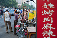 Young Muslim butcher selling meat in the street in the Muslim district of Daqingzhen Si in Xi'an, Shaanxi, China.