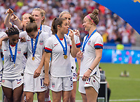 LYON,  - JULY 7: Kelley O'Hara #5, Becky Sauerbrunn #4 examine their medals during a game between Netherlands and USWNT at Stade de Lyon on July 7, 2019 in Lyon, France.