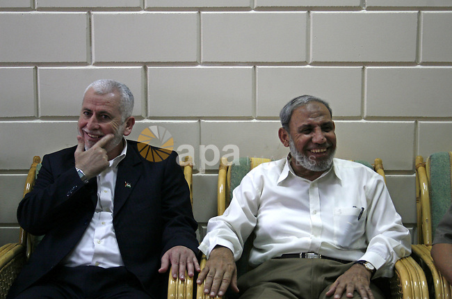 Palestinian senior Hamas official Mahmud Zahar (R) and former interior minister Said Siam (L) sit waiting to cross at the Rafah border terminal crossing between the southern Gaza Strip and Egypt. A Hamas delegation is due in Cairo for talks on a fragile three-week-old Gaza truce as Israel said it would reopen its borders with the territory at the Egyptian mediator's request.