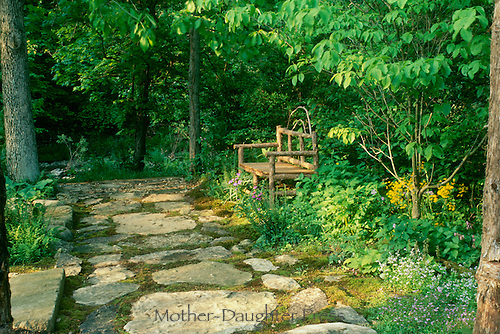 Bench in flagstone paved shade garden in spring with early morning light