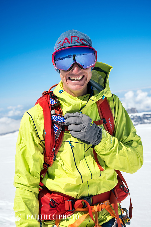 A skier stops and laughs about his backpack shoulder strap being a Snickers dispenser, while ski touring on the Berner Haute Route, Switzerland.