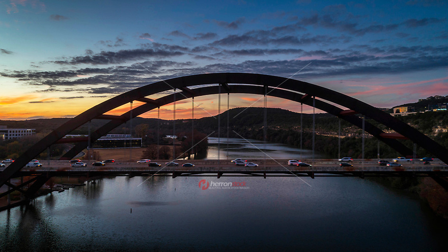 A beautiful sunset greets drive time traffic that spans across the 360 Bridge, an Austin icon, over Lake Austin providing access to Bee cave and Lake Travis.