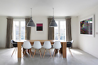A contemporary pale wood dining table is flanked by a set of Eames chairs in the open plan dining area