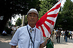 An older Japanese man holding a battle flag during the commemoration of the end of the Pacific war at Yasukuni Shrine, Kudanshita, Tokyo, Japan. August 15th 2010