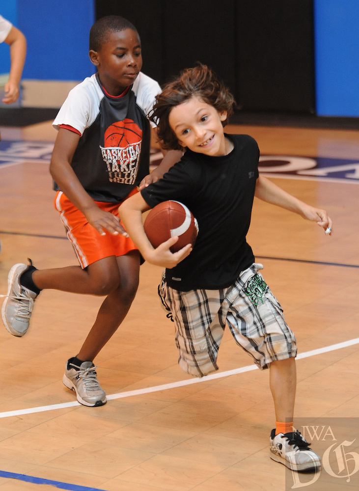 NWA Media/ANDY SHUPE - Laine Adams, 8, right, smiles as he carries the football as Brian Palmer, 8, reaches to make a touch tackle while enjoying a game of 7-on-7 football prior to leaving on a field trip to the Wilson Park Pool Wednesday, July 9, 2014 at the Yvonne Richardson Community Center in Fayetteville. The students are participating in the Summer Fun4Kids Camp, a summer camp being held at the center through Aug. 2.