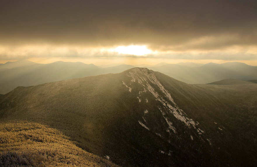 The early morning sun finds a hole to escape through on a cold November morning in New Hampshire's White Mountains.