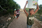 A boy carries water from a community water spigot provided by Servicio Social de las Iglesis Dominicanas in the Haitian community of Ganthier. SSID, a member of the ACT Alliance, has worked extensively in the community since it was devastated in 2016 by Hurricane Matthew.