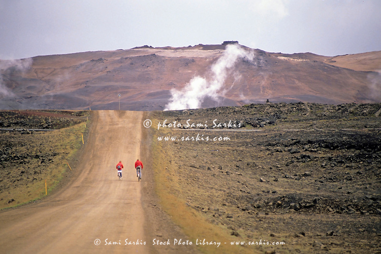 Two bikers on a dirt road leading to a geothermal power station at Myvatn, Iceland.