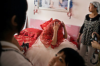 Newly-married bride Ren Jing removes her veil and dress after the wedding in Pingliang, Gansu, China.  The family is part of the Hui ethnic minority, a Muslim ethnic group native to northwestern China.