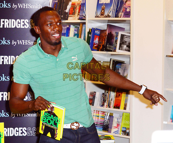 Usain Bolt<br /> Legendary Olympic athlete signs copies of his autobiography &quot;Faster than Lightning&quot; at Selfridges,Oxford Street, London, England.<br /> September 19th, 2013<br /> book signing half length top puma polo shirt  green goatee facial hair hand arm finger pointing    <br /> CAP/BF<br /> &copy;Bob Fidgeon/Capital Pictures