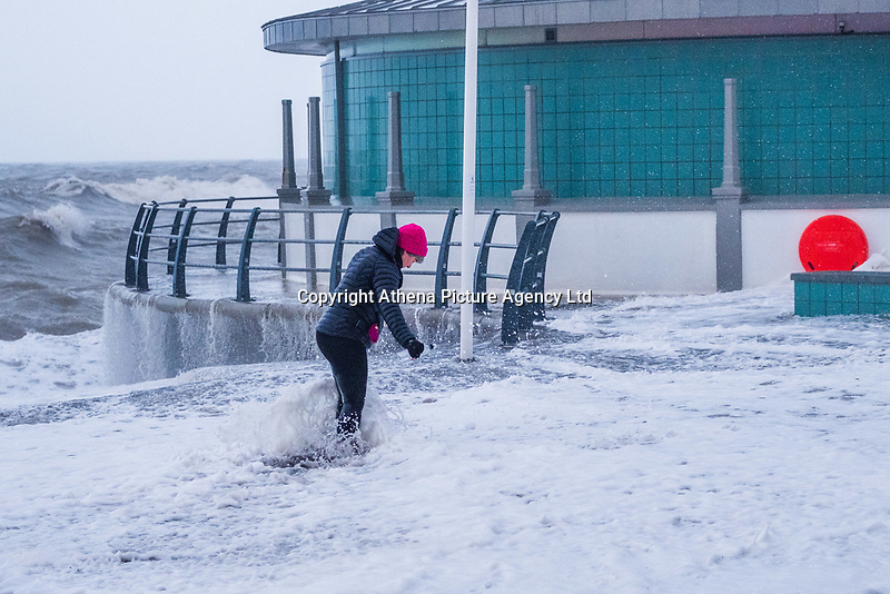 On the day after Storm Eleanor swept a trail of damage across the UK, strong westerly winds gusting over 75 mph whip the high Spring Tide into huge waves that batter the seafront at Aberystwyth, Wales, UK. Thursday 04 January 2017 <br />  <br /> A Woman gets a soaking from the waves as she walks along the promenade, which is covered in sand washed up from the beach by the storms<br /> <br /> A Yellow warning for wind  have been issued by the Met Office for virtually  the whole of England and Wales until 19.00 tonight, with the risk of damage and disruption to power supplies and travel greatest on the western shores of the country