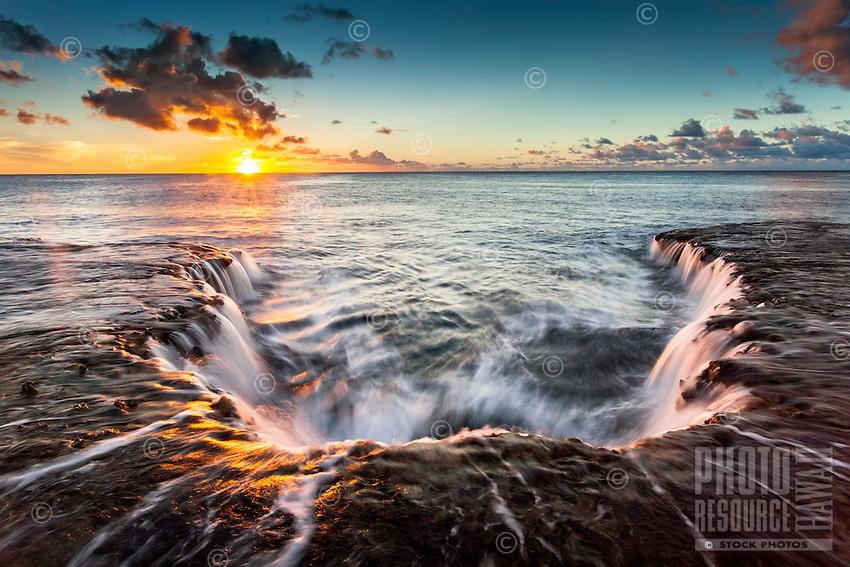 Water cascades off of a rocky shelf under a golden sunset at Shark's Cove, North Shore, O'ahu.