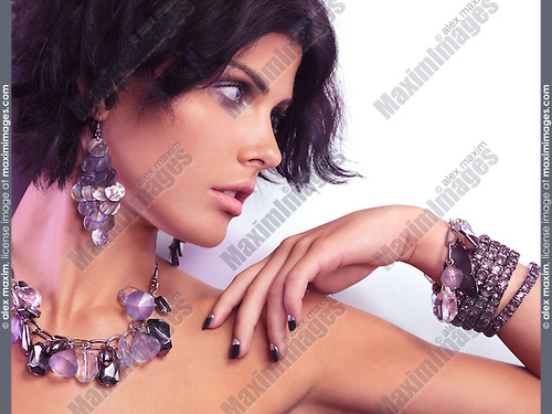 Beauty portrait of a young glamorous woman wearing jewellery with purple stones