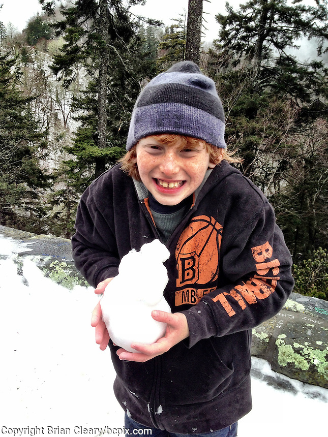 A boy holds a miniature snowman he made in the snow near Cherokee, NC, iPhone photo from the archive at bcpix.com. (Photo by Brian Cleary/www.bcpix.com)