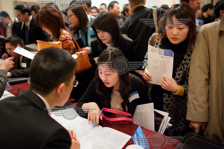 Chinese-American financial professionals and Chinese people studying or working in the United States meet with recruiters for companies from Shanghai, during a recruitment event.