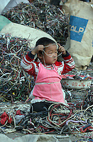 A child plays in a junkyard where wires of electronic trash are stripped in Guiyu, China March 8, 2005. For years, developed countries have been exporting tons of electronic waste to China for inexpensive, labor-intensive recycling and disposal.