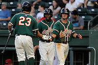 Second baseman Avery Romero (1) of the Greensboro Grasshoppers, right, is congratulated after scoring a run in a game against the Greenville Drive on Wednesday, May 7, 2014, at Fluor Field at the West End in Greenville, South Carolina. Romero is the No. 9 prospect of the Miami Marlins, according to Baseball America. Greenville won, 12-8. (Tom Priddy/Four Seam Images)