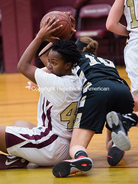 WATERBURY, CT- 11 January 2015-011116EC08-    Sacred Heart's Mahnue Sahn manages to pass the ball while Woodland's Carla Piccolo gets tripped up from behind. Erin Covey Republican-American