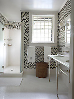 The walls of this bathroom have been hand-painted with a black and white geometric design
