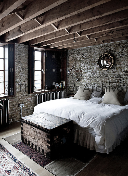 An old travel chest at the end of the bed adds to the rugged, industrial aesthetic of the bedroom, which also has exposed brick work and ceiling