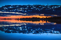 Natthimmel med moln i solnedgång speglas i vatten vid Biskopsö i skärgården