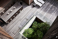 A view from above of an outdoor terrace area with a dining table and chairs and sun loungers on wooden decking.