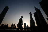 A pedestrian walks under towers of China's state banks in the Pudong Financial District in Shanghai, China. Bank of China, one of the four big state banks in China, said on Monday it would strengthen its internal risk controls ahead of its initial public offering - an estimated $8 billion (Euro 6.67 billion) share sale planned for later this year. The announcement came only a week after two former branch managers were charged in the United States with a scheme to defraud the bank of $485 million (Euro 404 million) over 13 years..