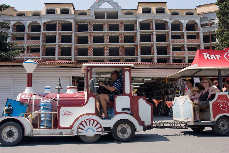 Sunny Beach, Nesebar, Bulgaria..Tourists ride a bus past unfinished apartments at Sunny Beach, the largest holiday resort in the Balkans, and a popular destination for cheap foreign package tours. Rapid overdevelopment of the Back Sea coast has led to widespread environmental destruction, and many properties lie uncompleted or empty.