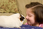 5 year old girl with pet guinea pig, closeup, nose to nose