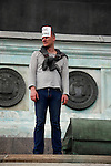 Reve General, May Day March, Paris, 1 May 2009. Man in sailor shirt standing on the July Monument at the Place de la Bastille with Reve General sticker on his head.