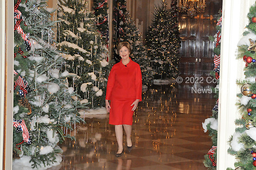 """Washington, DC - December 3, 2008 -- First lady Laura Bush walks through the Cross Hall en route to the East Room to make remarks during a media preview of the 2008 holiday decorations and tasting event on the State Floor of the White House in Washington, D.C. on Wednesday, December 3, 2008.  The theme of this years decorations is """"a Red, White, and Blue Christmas""""..Credit: Ron Sachs / CNP"""