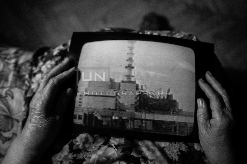 Old woman - witness of the Chernobyl catastrophe holds the picture of the 4th reactor of the the Chernobyl nuclear power plant after devastation