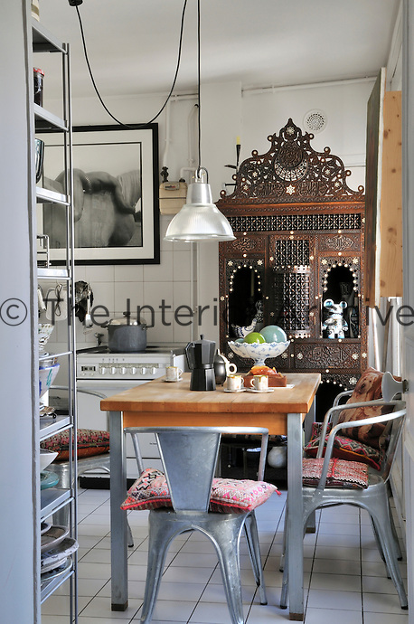 In the kitchen an intricately carved Indian cupboard fits neatly into an alcove next to the cooker and creates an interesting contrast to the utilitarian 30's C armchairs by Xavier Pauchard for Tolix