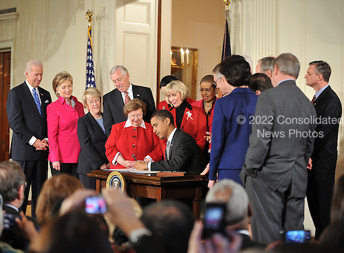 "Washington, DC - January 29, 2009 -- United States President Barack Obama signs the Lilly Ledbetter Fair Pay Restoration Act in the East Room of the White House in Washington, DC on Thursday, January 29, 2009.  The act ""makes it easier for women and others to sue for pay discrimination, even if the discrimination has prevailed for decades"".  Visible from left to right: Vice President Joseph Biden; Secretary of State Hillary Rodham Clinton; United States Senator Patty Murray (Democrat of Washington); United States House Majority Leader Steny Hoyer (Democrat of Maryland); United States Senator Barbara Mikulski (Democrat of Maryland); President Obama; Lilly Ledbetter; Delegate Eleanor Holmes Norton (Democrat of the District of Columbia); and United States Senator Harry Reid (Democrat of Nevada)..Credit: Ron Sachs - CNP"