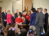 """Washington, DC - January 29, 2009 -- United States President Barack Obama signs the Lilly Ledbetter Fair Pay Restoration Act in the East Room of the White House in Washington, DC on Thursday, January 29, 2009.  The act """"makes it easier for women and others to sue for pay discrimination, even if the discrimination has prevailed for decades"""".  Visible from left to right: Vice President Joseph Biden; Secretary of State Hillary Rodham Clinton; United States Senator Patty Murray (Democrat of Washington); United States House Majority Leader Steny Hoyer (Democrat of Maryland); United States Senator Barbara Mikulski (Democrat of Maryland); President Obama; Lilly Ledbetter; Delegate Eleanor Holmes Norton (Democrat of the District of Columbia); and United States Senator Harry Reid (Democrat of Nevada)..Credit: Ron Sachs - CNP"""