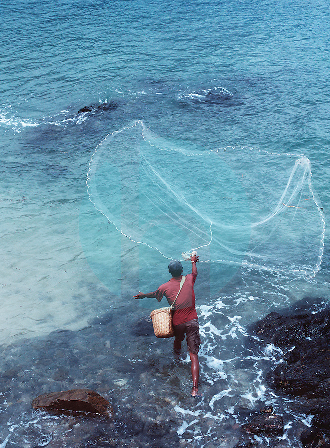 March 21st, 2004-Dili, Timor-Leste-A man casts his fishing net into the surf just east of Dili, near Cristo Rei Beach in Dili District.  Photograph by Daniel J. Groshong/Tayo Photo Group