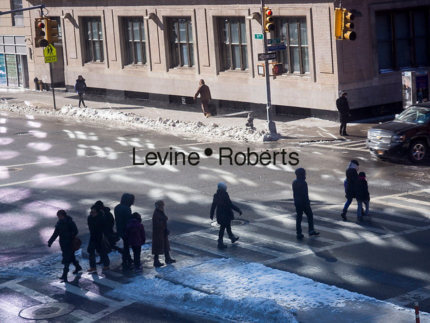 Pedestrians cross Ninth Avenue in Chelsea in New York on Friday, January 24, 2014. (© Richard B. Levine)