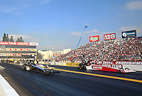 Feb 9, 2014; Pomona, CA, USA; NHRA top fuel dragster driver Khalid Albalooshi (near lane) races alongside Steve Torrence during the Winternationals at Auto Club Raceway at Pomona. Mandatory Credit: Mark J. Rebilas-