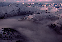 Morning fog fills valleys between Colorado's snow-capped San Juan Mountains.  A fresh dusting of snow covers the remote trails  of the Alpine Loop part of 135,000 acres of deep glaciated valleys cut through a rugged volcanic terrain.  The former mining district has 11 Wilderness Study Areas and in managed to maintain a wide variety of recreational activities.