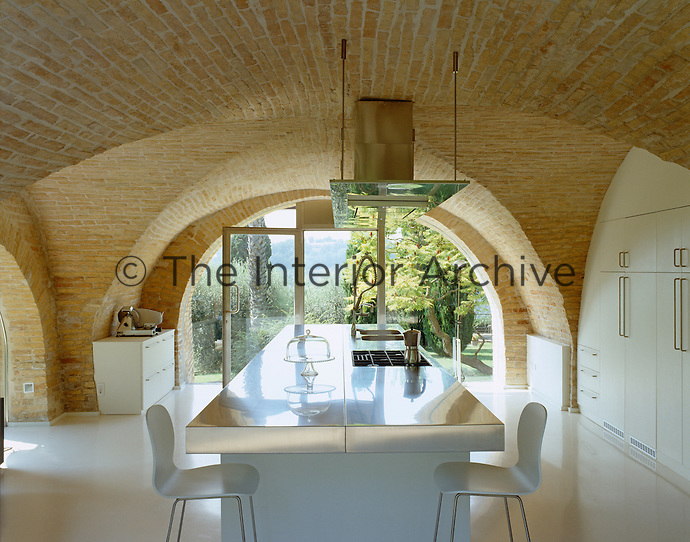 The window in the vaulted kitchen is recessed directly into the curved wall and the units are by Boffi