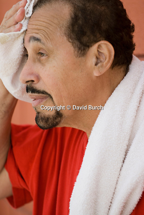 Mature hispanic man wiping forhead after workout