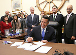 Surrounded by lawmakers and staff members, Nevada Gov. Brian Sandoval signs into law an unprecedented package of incentives to bring Tesla Motors' $5 billion battery factory to the state, at the Capitol, in Carson City, Nev., on Thursday, Sept. 11, 2014. (AP Photo/Cathleen Allison)